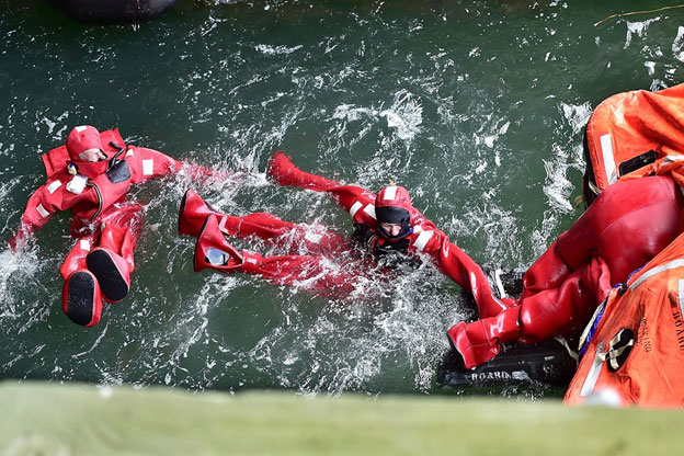 Students in immersion suits climb into a raft as part of a safety and survival training program, US Coast Guard Sector Northern New England, Maine